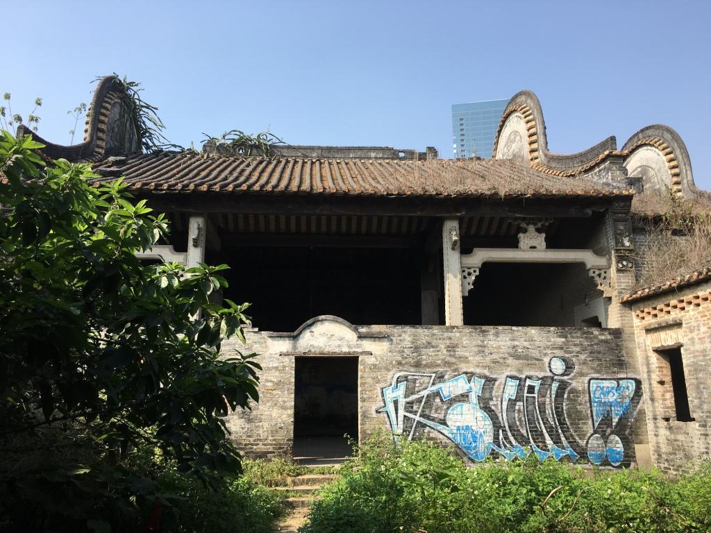 Разрушенные, поросшие зеленью и испещренные граффити и портретами Мао родовые храмы и деревенские дома на фоне строящихся небоскребов